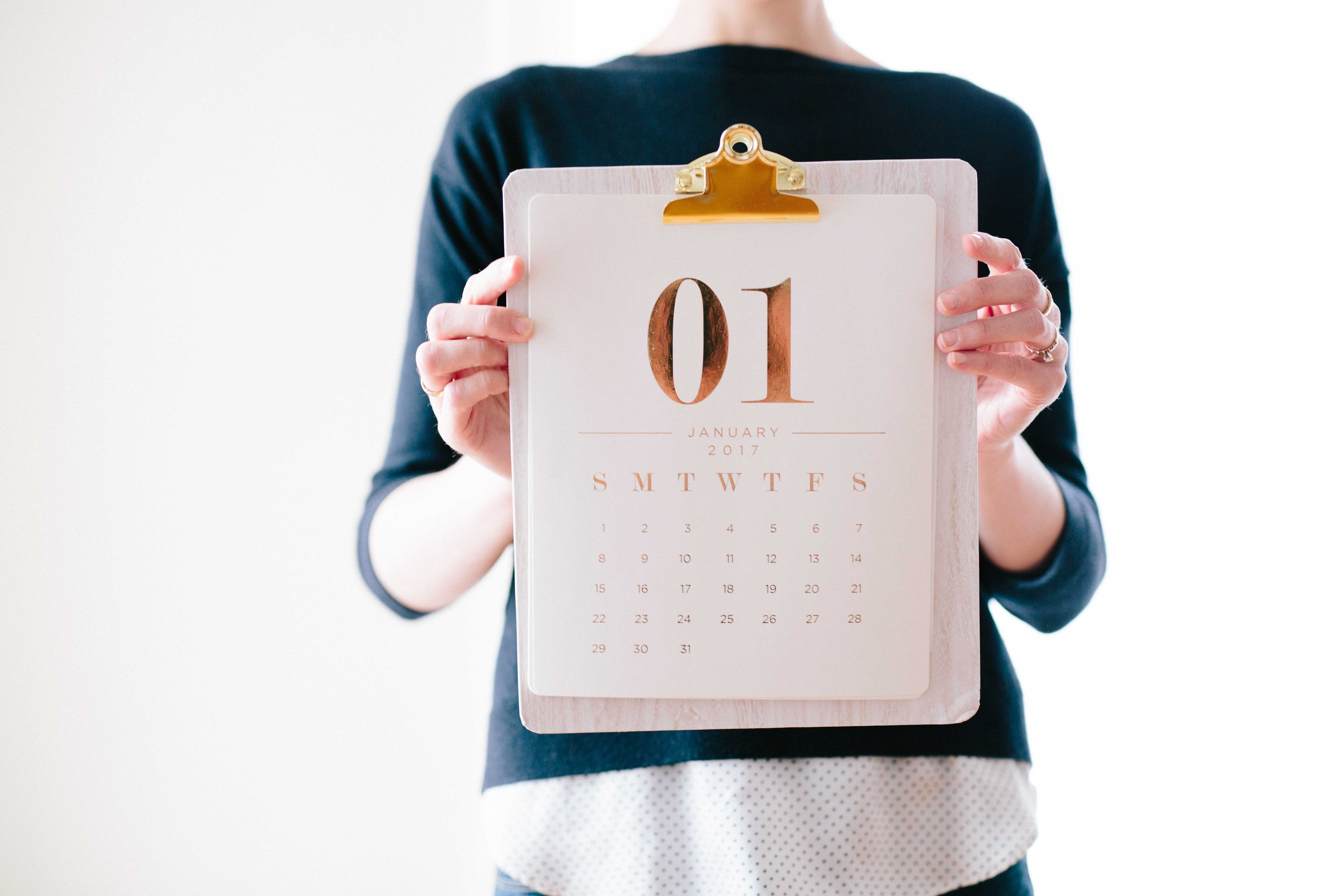 someone holding a clipboard with a January calendar on it