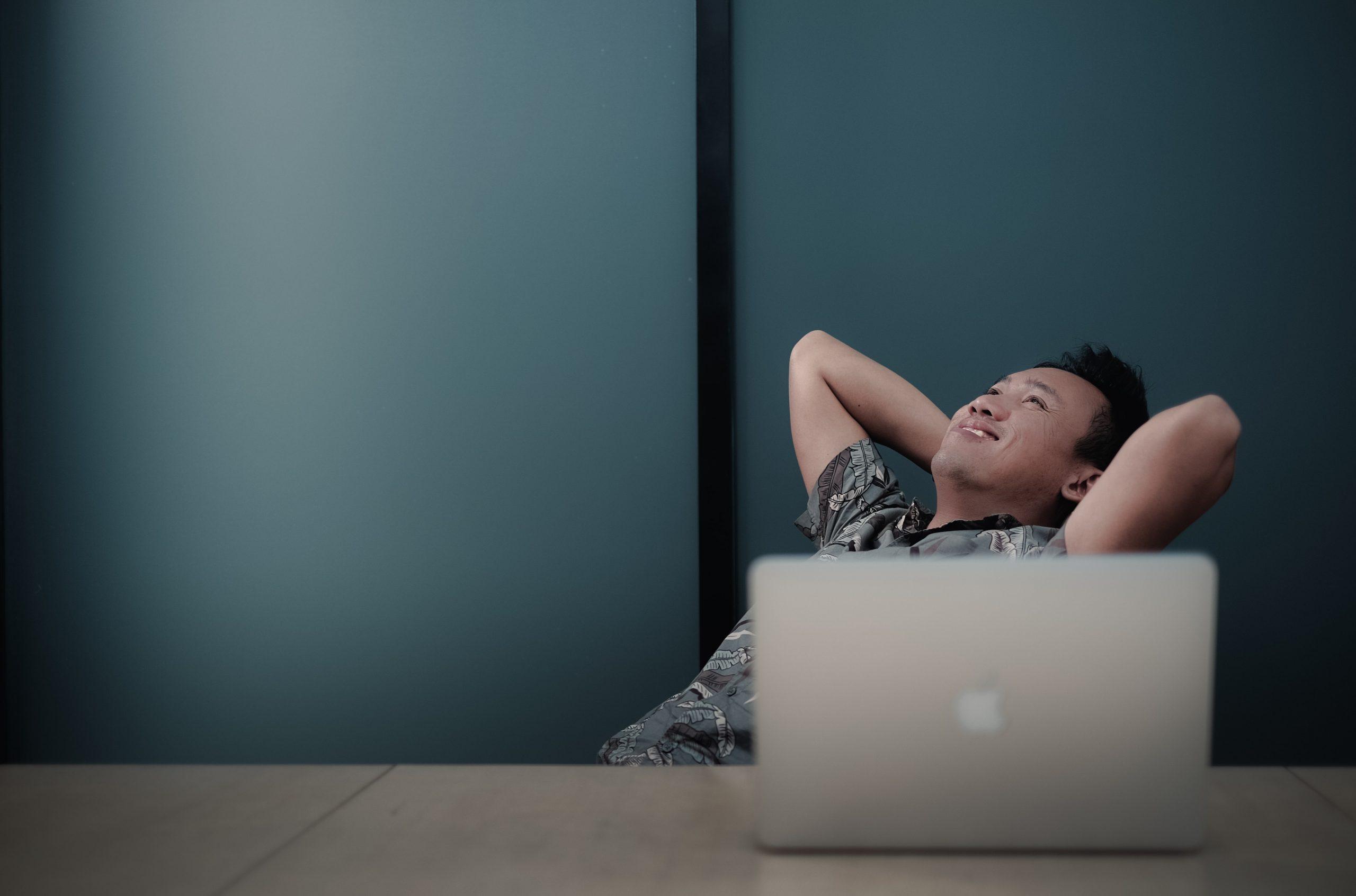 Happy man sitting behind a laptop